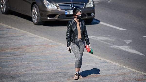 Девушка в маске и перчатках идет по улице - Sputnik Грузия