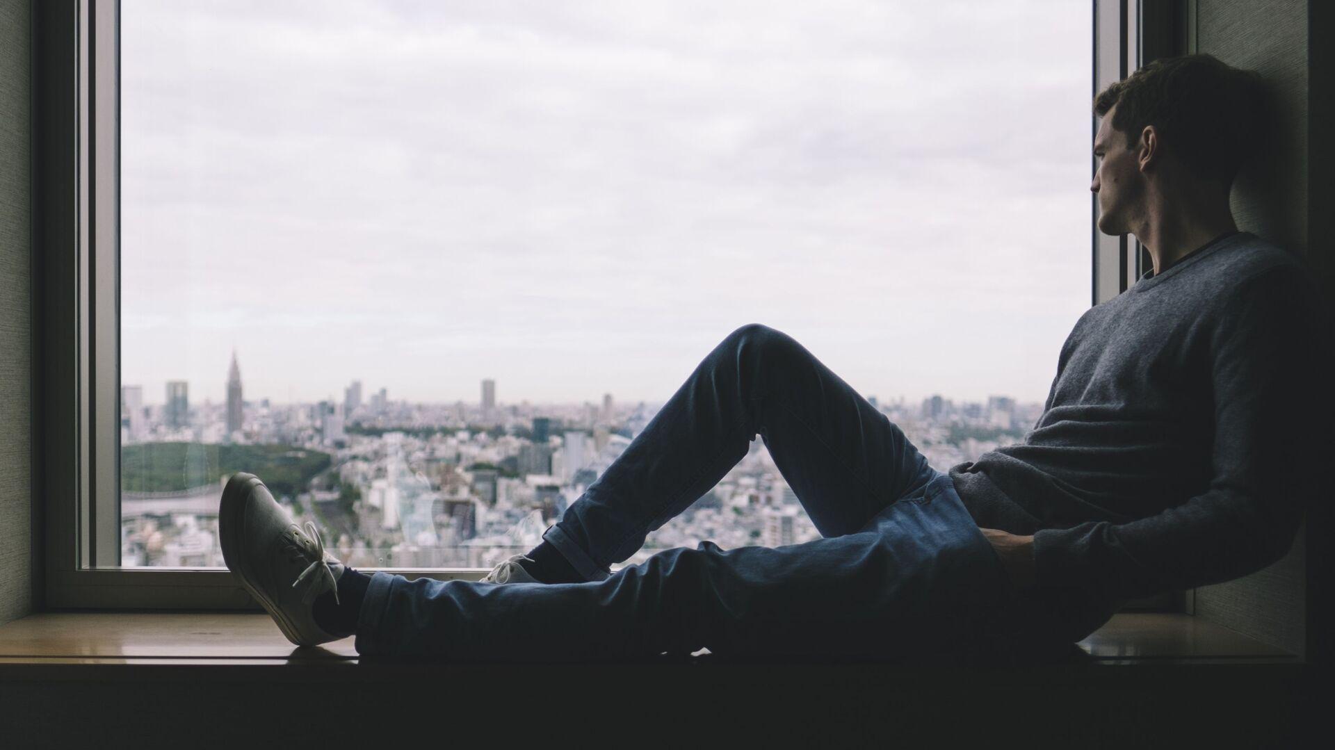 Самоизоляция. Молодой человек сидит на подоконнике и смотрит в окно - Sputnik Грузия, 1920, 17.09.2021