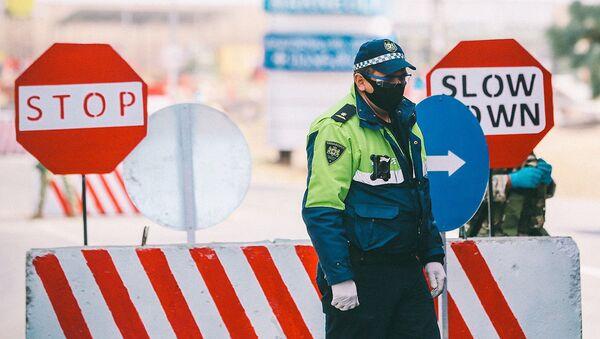 Полицейские на блокпосту во время эпидемии коронавируса проверяют автомашины - Sputnik Грузия