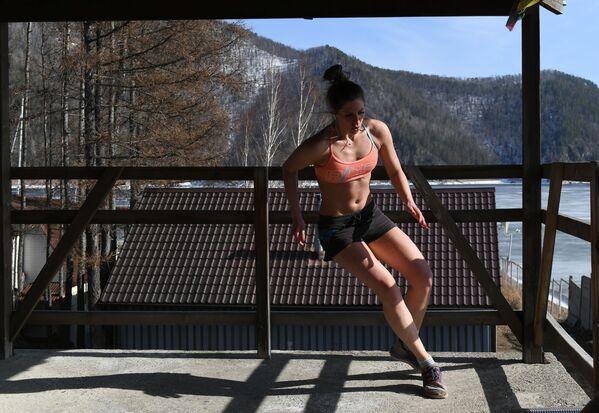 Сноубордистка Юлия Бояринцева во время ежедневной тренировки по общей физической подготовке и йоге на балконе загородного дома   - Sputnik Грузия