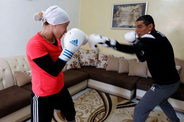 Спортсменка Марием Хомрани тренируется со своим тренером и мужем Имедом Заяни дома во время самоизоляции в Тунисе - Sputnik Грузия