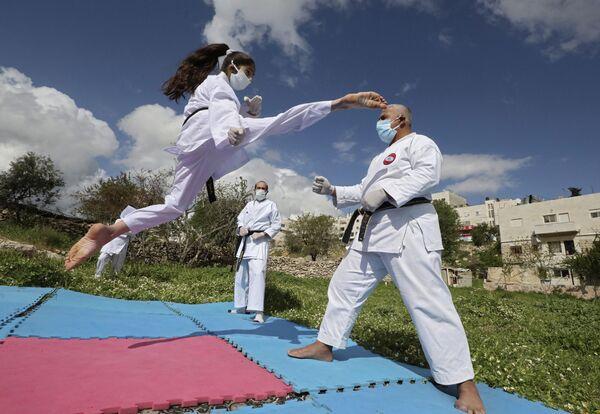 Палестинская чемпионка по карате во время тренировки со своим отцом дома в Хевроне  - Sputnik Грузия