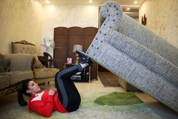 Иорданская дзюдоистка Хадиль Алами использует диван во время домашней тренировки на самоизоляции   - Sputnik Грузия