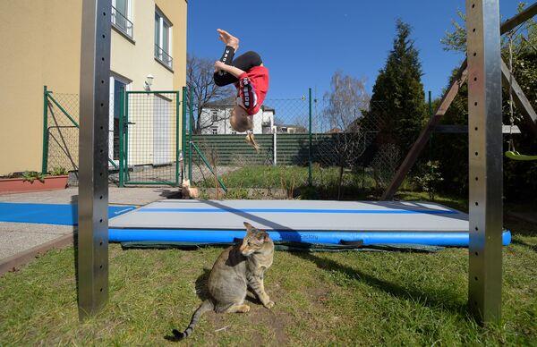 Гимнастка Феня Лоренц тренируется в саду дома своих родителей на самоизоляции - Sputnik Грузия
