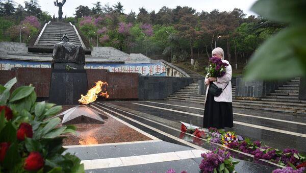 День Победы 9 мая 2020 года в парке Ваке. Женщина с цветами у Вечного огня и у Могилы Неизвестного Солдата - Sputnik Грузия