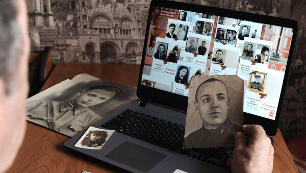 Мужчина смотрит онлайн-трансляцию акции Бессмертный полк - Sputnik Грузия