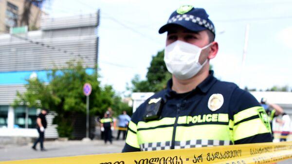 Сотрудник полиции и пожарные-спасатели на месте чрезвычайного происшествия - Sputnik Грузия