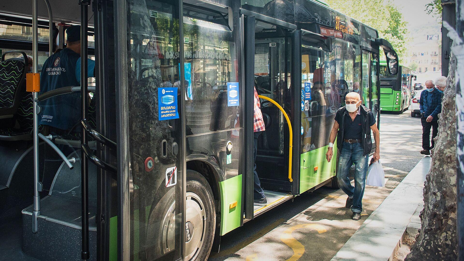 Городской транспорт. Пассажирский автобус и люди на остановке - Sputnik Грузия, 1920, 13.09.2021