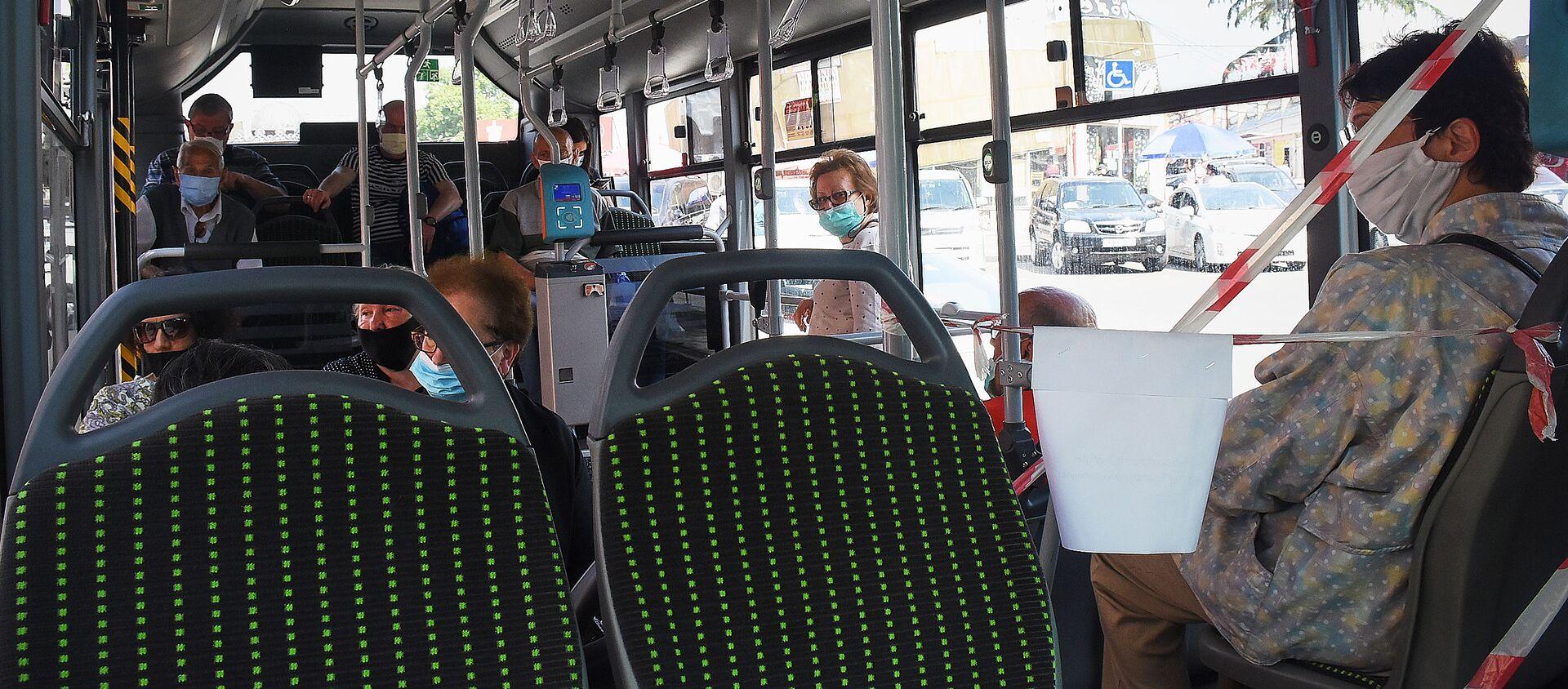 Городской транспорт. Пассажиры в масках едут в автобусе - Sputnik Грузия, 1920, 28.01.2021