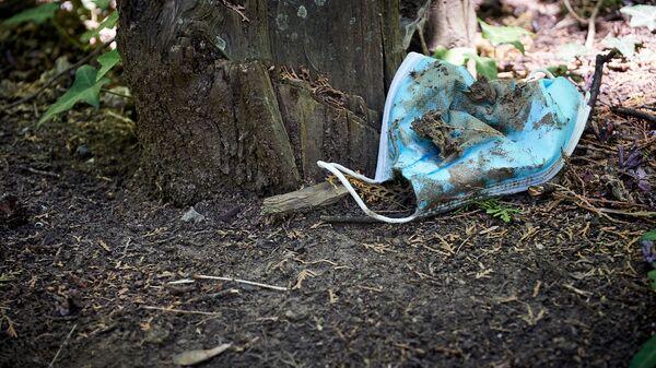 Выброшенная на землю в парке медицинская маска - Sputnik Грузия