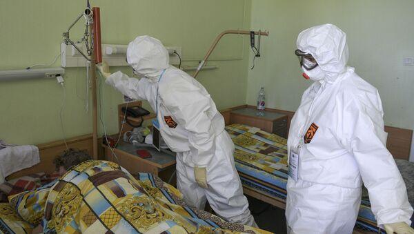 Медицинские работники осматривают пациента в госпитале COVID-19 в больнице No 122 им. Л. Г. Соколова в Санкт-Петербурге - Sputnik Грузия