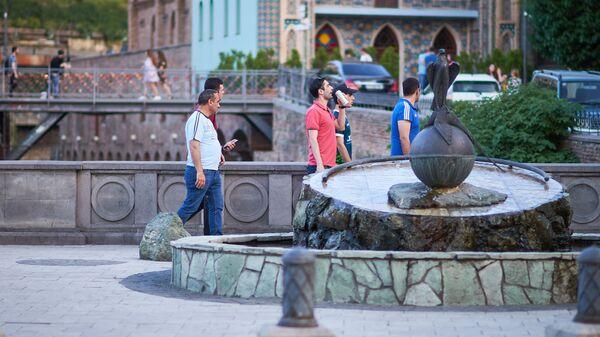 Жители города и туристы гуляют по району Абанотубани у памятника соколу и фазану - Sputnik Грузия