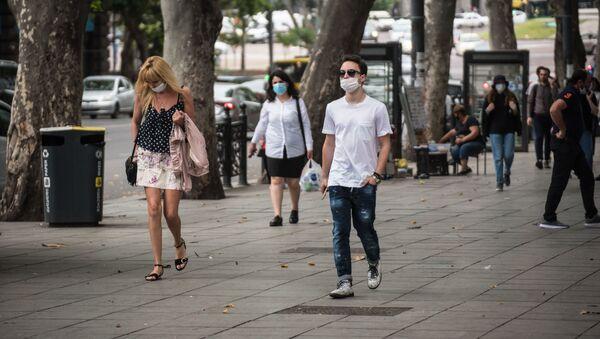 Люди идут по проспекту Руставели в защитных масках во время пандемии коронавируса - Sputnik Грузия