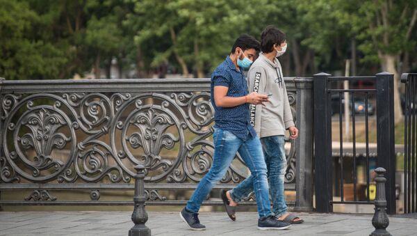 Молодые мужчины идут по центру города в защитных масках - Sputnik Грузия