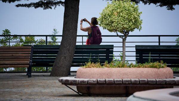 Парк Мтацминда. Утро. Редкие посетители на аллеях парка. Женщина фотографирует город со смотровой площадки у фонтана - Sputnik Грузия